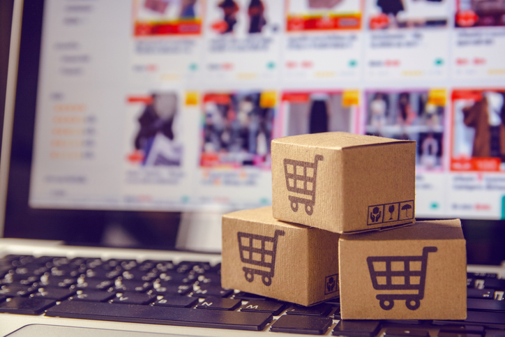 Online shopping : Paper cartons or parcel with a shopping cart logo on a laptop keyboard. Shopping service on The online web and offers home delivery.