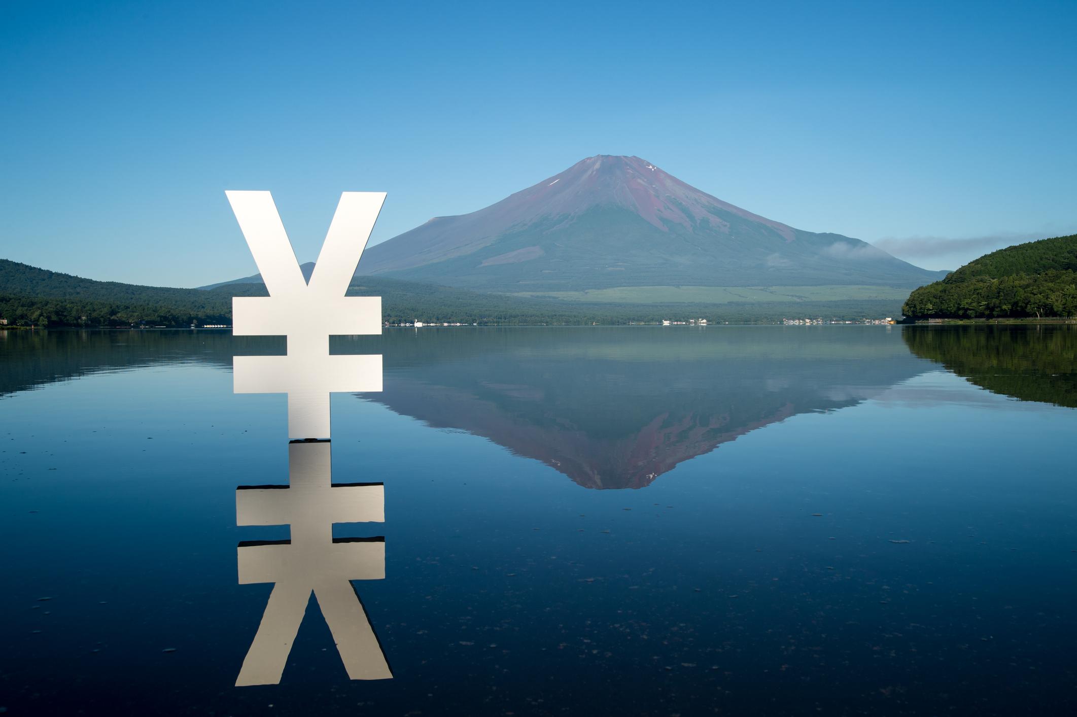 Japanese currency Yen shape object and its reflection in Yamanaka lake near by Mt. Fuji in Shizuoka Prefecture.