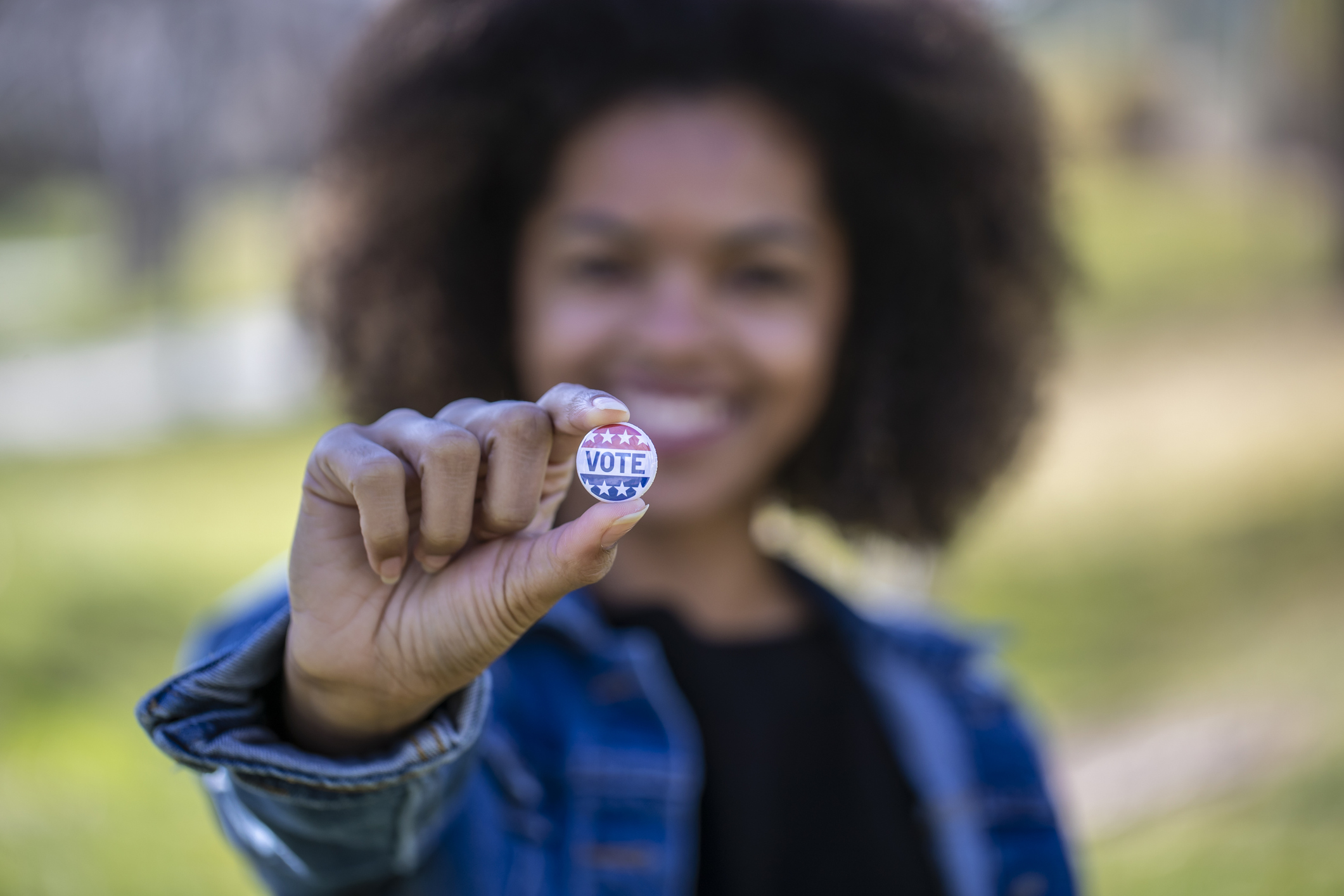 A young African American woman holding a voting badge.