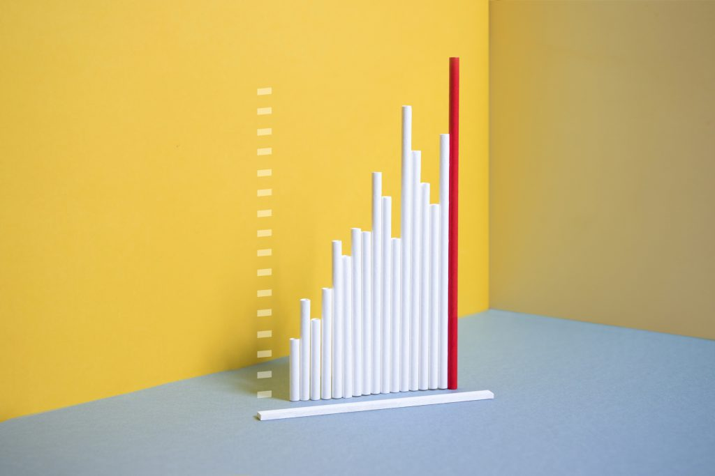 Tallest singled out red bar in a row of ascending blue bar on yellow background.